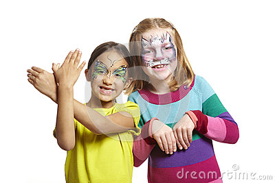 Young girls with face painting of cat and butterfly