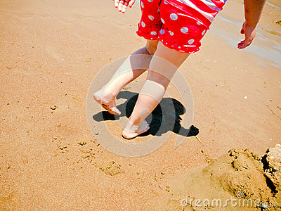 Young girls feet and legs walking on the beach