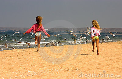 Young girls happily running towards seagulls