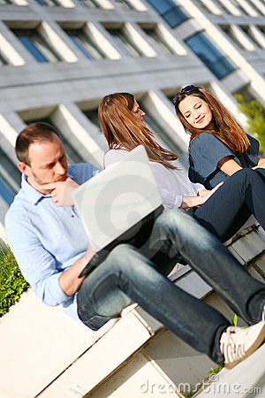 Young girls outdoors and man with laptop