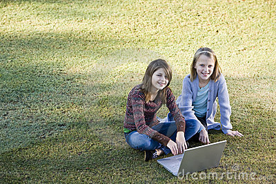 Young girls using laptop on grass