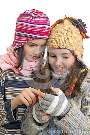 Young girls in warm winter clothes speaking on a mobil