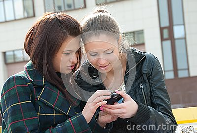 Young girls watch something in mobile phone