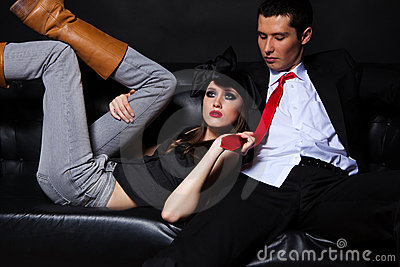 Young glamourous loving couple on black sofa.