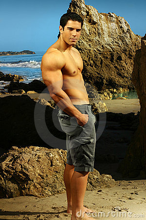 Young goodlooking fitness male model at a beach