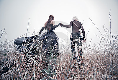 Young goth couple walking on field