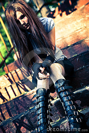 Young goth woman sitting on stairs
