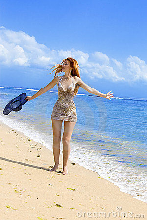 Young graceful woman goes on coast of ocean with s