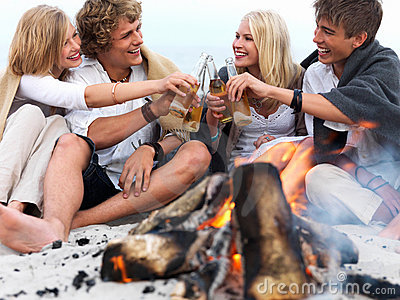Young group of people sitting by bonfire at the be