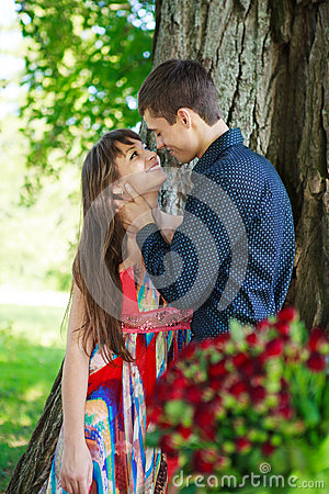 Young guy affectionately hugs girl in a sunny nature