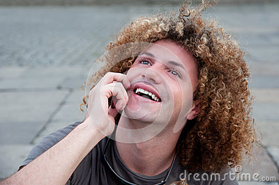 Young guy with curly hair talk on cellphone