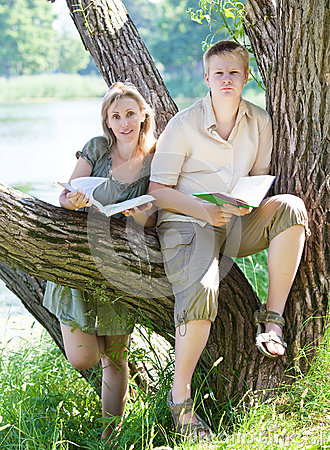 Young guy and the girl prepare for lessons, examination in spring park near lake