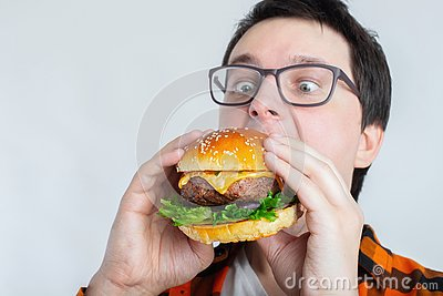 A young guy with glasses holding a fresh Burger. A very hungry student eats fast food. Hot helpful food. The concept of gluttony a Stock Photo