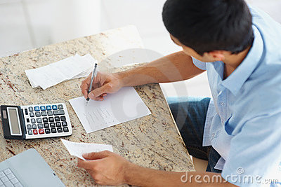 Young guy paying bills using calculator