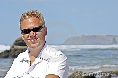 Young guy smiling at the atlantic ocean