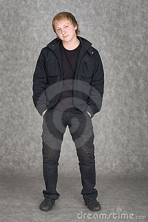 Young guy standing on a grey background