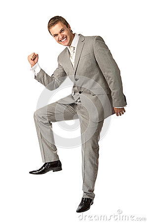 Young guy in suit clenching his fist in triumph