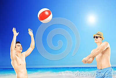 Young guys playing with a ball, next to a sea
