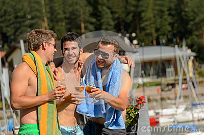 Young laughing guys in swimsuits drinking beer