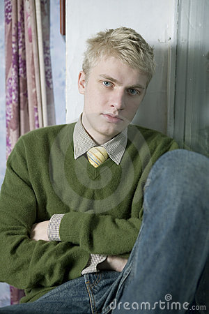 Young handsome blond man in green sweater