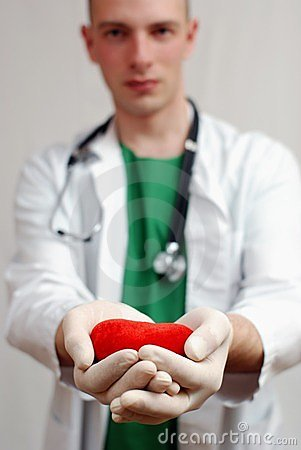 Young handsome doctor holding heart in hands