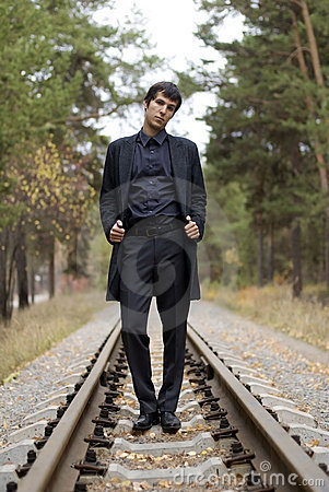 Young handsome guy on a rail road