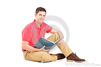 Young handsome guy sitting on a floor and reading a book