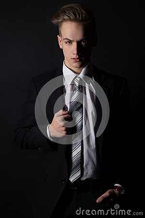 Young handsome man in a business suit and a white shirt and tie in formal style in the Studio on a black background Stock Photo