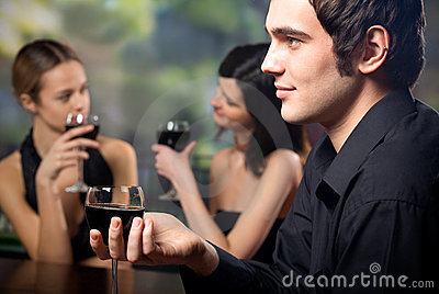 Young handsome man with glass of red-wine and two women
