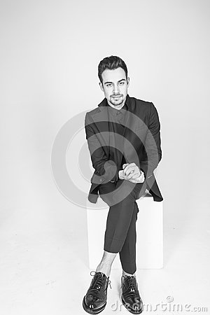 Free Young Handsome Man In A Black Suit, Sitting, Seriously Looking A Stock Photos - 117140293