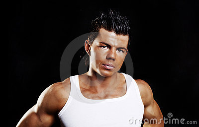 Young handsome man with muscles over dark