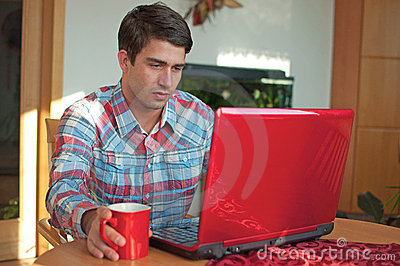 Young handsome man sitting with coffee and laptop