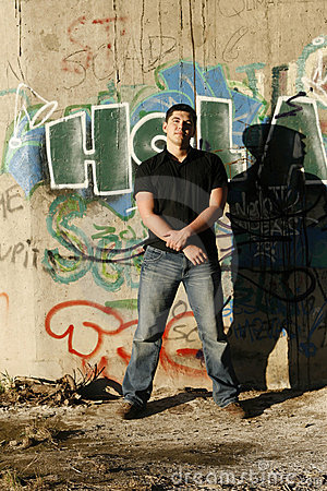 Young handsome man standing by the graffiti wall
