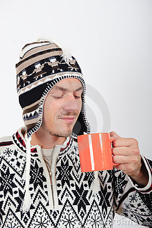 Young handsome winter man with cup of tea