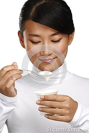 Young happy asian woman eating fresh yogurt
