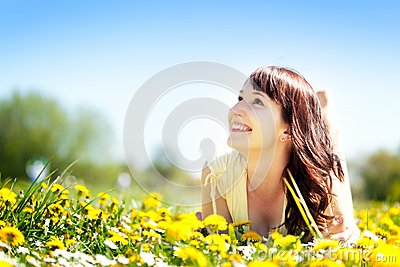 Young happy beautiful woman lying on grass, flowers Stock Photo