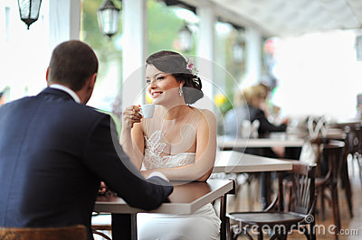 Young happy bride and groom at an outdoor cafe