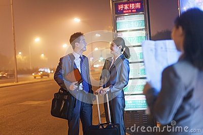 Young happy business people waiting for a bus at night