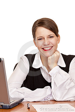 Young happy business woman sits on desk in office