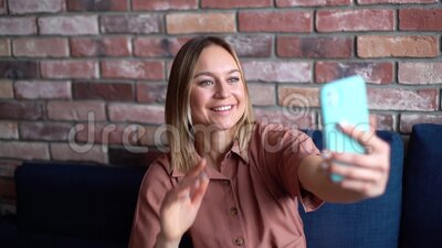 Young happy business woman talking video chat using mobile phone and waves hand. Young happy business woman talking video chat using mobile phone and waves her stock video footage