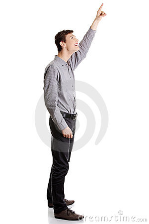 Young happy businessman pointing up