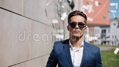 Young happy businessman scatter the dollars in the street. It is located near the office center, slow motion. Money rain. Successful business or winning the stock video footage