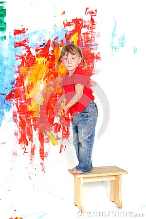 Young happy child girl painting white wall