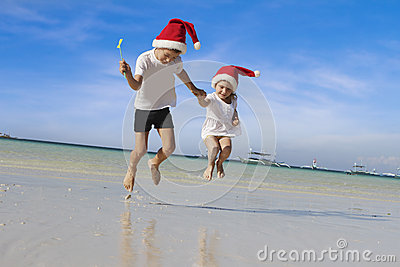 Young happy children in santa hats on tropical beach backgro