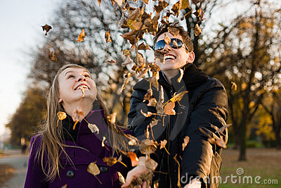 Young happy couple with autumn leaves