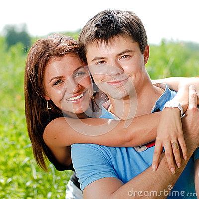 Young happy couple embracing and smiling outdoors