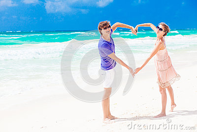 Young happy couple on honeymoon making heart shape