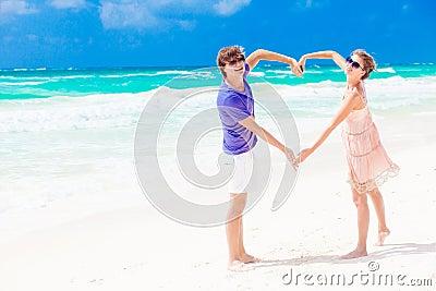 Young happy couple on honeymoon making heart shape