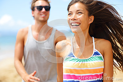 Young happy couple laughing having fun on beach