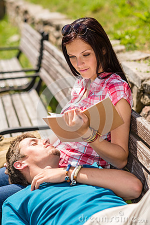 Young happy couple relax on bench park